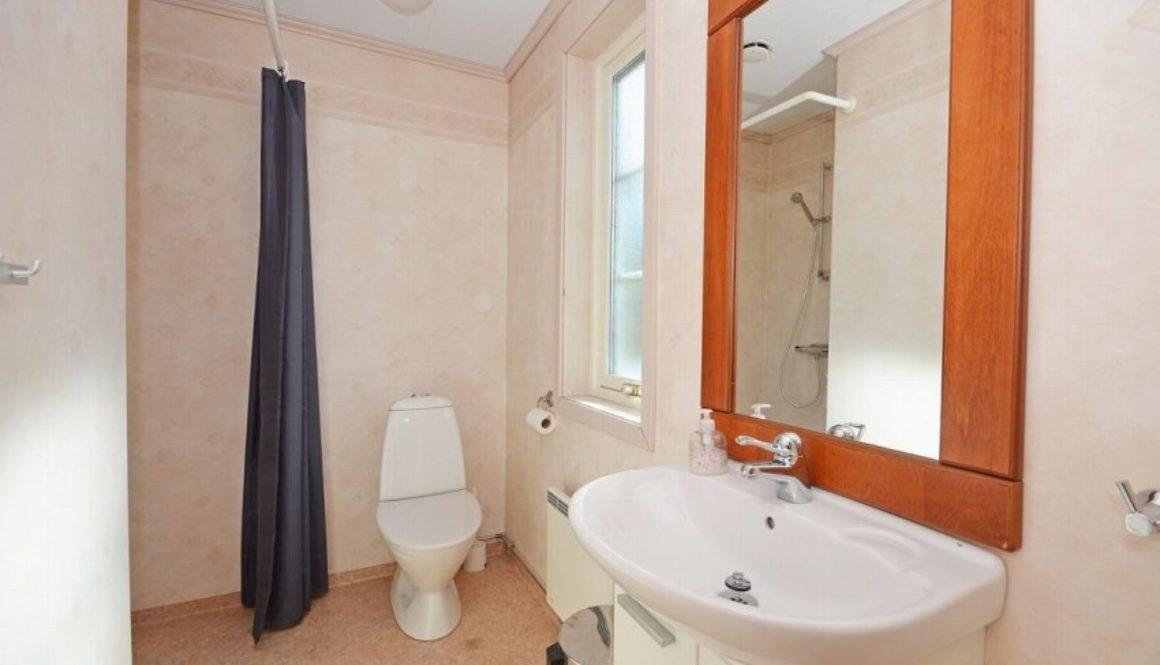 Dusjbad med wc, servant på innredning og dusjnisje